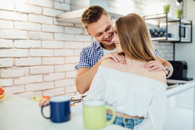 De casal na cozinha, homem fazendo massagem para sua mulher. Foto Premium