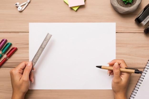 De cima mãos segurando régua e caneta sobre a folha de papel em branco Foto gratuita