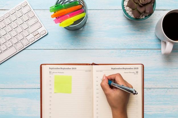 De cima mulher escrevendo no diário Foto gratuita