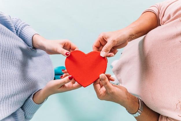 De cima mulheres segurando coração Foto gratuita