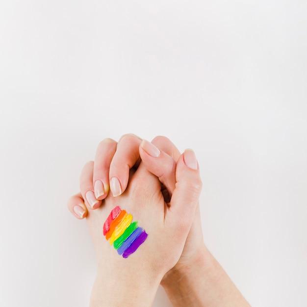 De mãos dadas com uma bandeira do orgulho pintado Foto gratuita