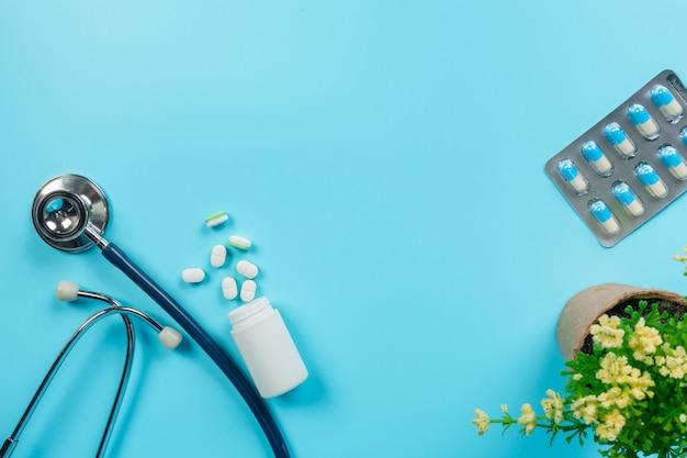 De medicina, suprimentos médicos colocados com ferramentas de médico em um azul. Foto gratuita