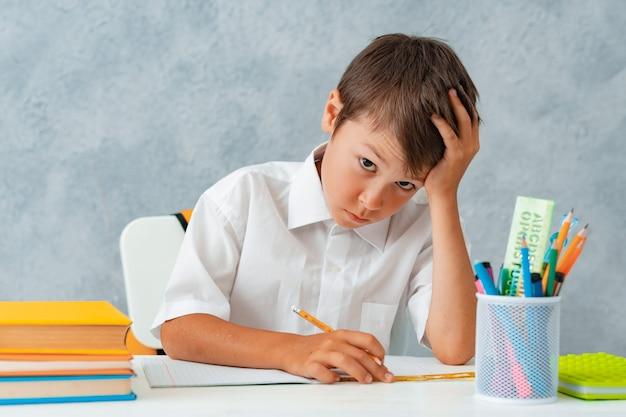 De volta à escola. aluno sorridente feliz desenha na mesa. Foto gratuita