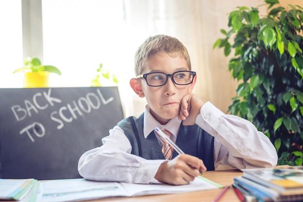 De volta à escola. bonita criança sentada na recepção na sala de aula. Foto Premium