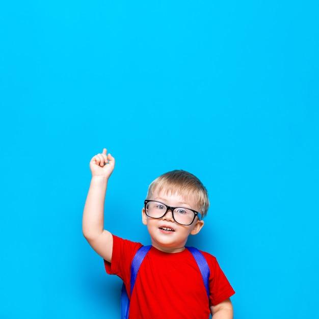 De volta à escola estilo de vida júnior de primeiro grau. menino pequeno no t-shirt vermelho. feche acima do retrato da foto do estúdio do menino de sorriso nos vidros com schoolbag, apontando acima com seu dedo Foto Premium