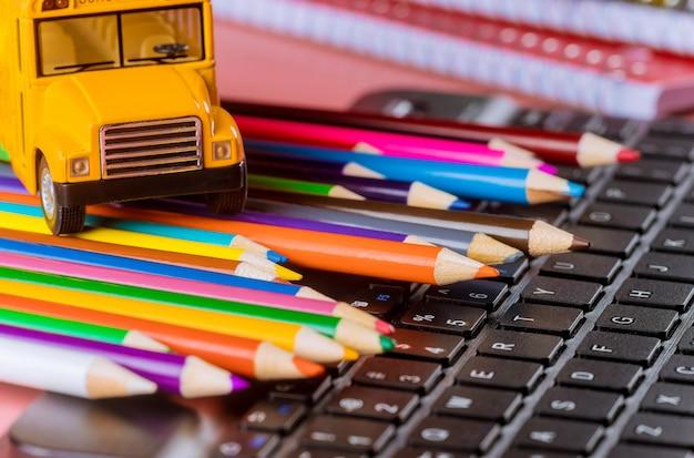 De volta à escola, ônibus escolar em lápis de cor e teclado Foto Premium