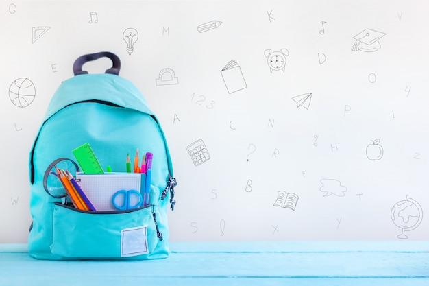 De volta à escola. trouxa completa da escola de turquesa com artigos de papelaria na tabela. Foto Premium