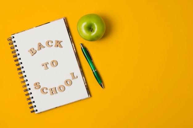 De volta ao bloco de notas da escola com fundo laranja Foto gratuita