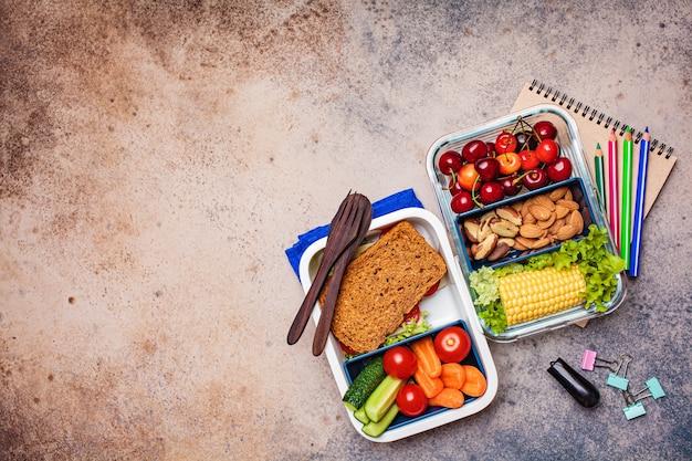 De volta ao conceito de escola. lancheira com alimentos frescos saudáveis. sanduíche, legumes, frutas e nozes em um recipiente para comida, fundo escuro. Foto Premium