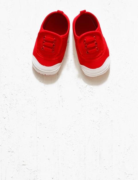 De volta ao fundo da escola - sapatas de lona tamanho pequeno vermelho bonito infantil vista superior Foto Premium