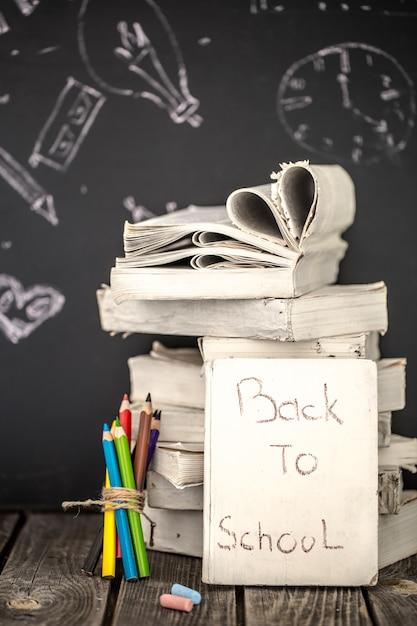De volta às aulas, pilha de livros e material escolar no fundo do quadro-negro pintado com giz, conceito de educação Foto gratuita