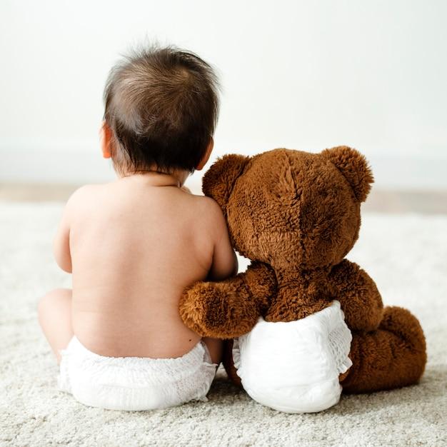 De volta de um bebê com um ursinho de pelúcia Foto Premium