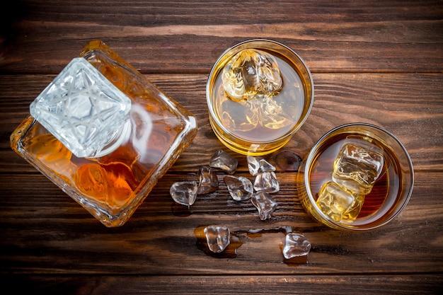 Decander e dois copos com gelo e uísque Foto Premium