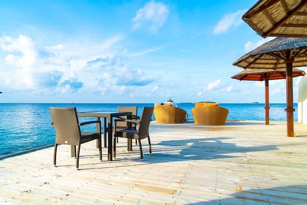 Deck do pátio ao ar livre vazio e cadeira com oceano azul nas maldivas Foto Premium