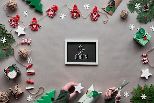 Decoração artesanal criativa, quadro de natal sem desperdício. vista plana leiga, superior em papel ofício. bugigangas têxteis, caixa de presente de papel decorada na mão. xmas eco amigável. texto