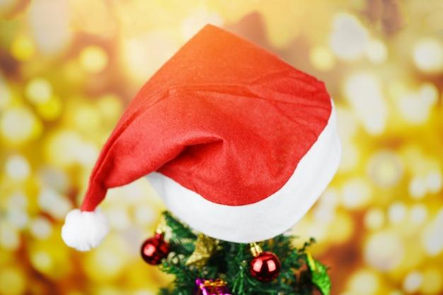 Decoração bonita chapéu de natal - árvore de natal com papai noel chapéu vermelho bola caixa de presente estrela e luzes decoradas pinheiro celebração do festival de férias de ano novo Foto Premium