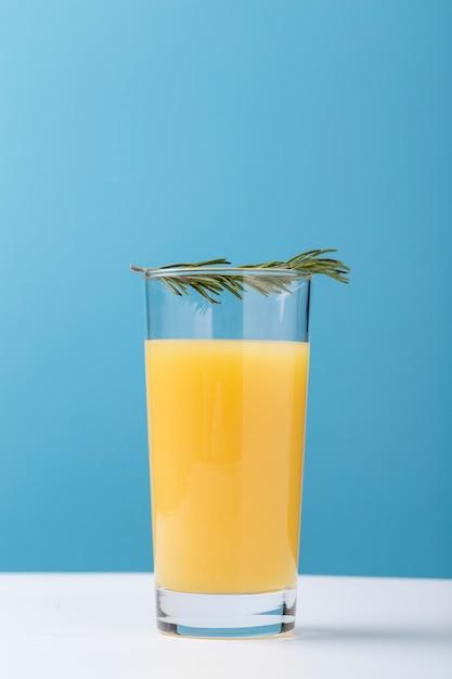 Decoração com copo de suco de laranja e ervas Foto gratuita