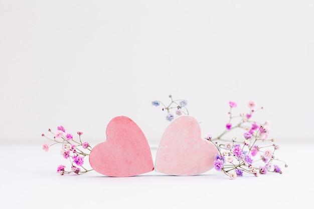 Decoração com corações e flores sobre fundo branco Foto Premium