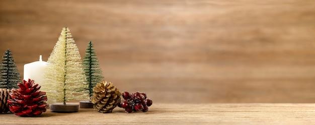 Decoração da árvore de natal na mesa com neve. pinha, visco e bola de sino pendurado na parede Foto Premium
