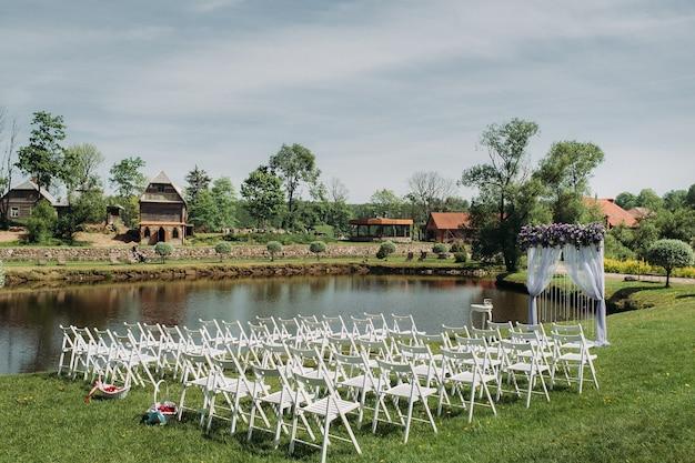 Decoração da cerimônia de casamento no verão, perto do lago, na grama verde. cerimônia de casamento lindamente decorada. Foto Premium