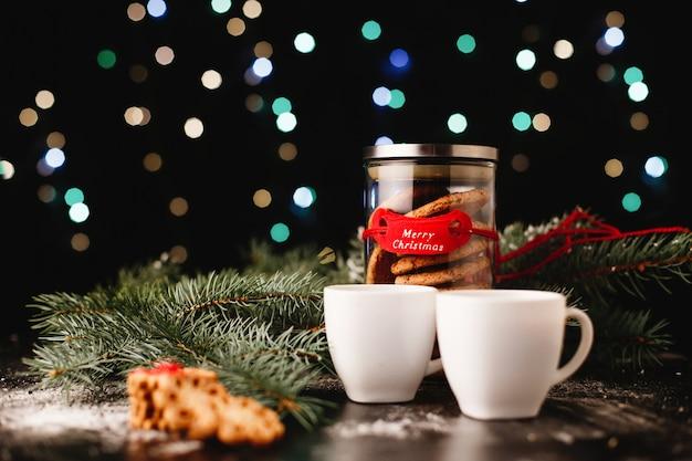 Decoração de ano novo e natal. garrafa com biscoitos de chocolate e xícaras para chá Foto gratuita