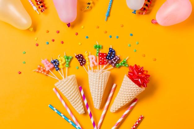 Decoração de cone decorativo feliz aniversário no pano de fundo amarelo Foto gratuita