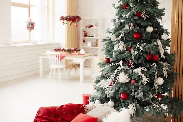 Decoração de feriados de inverno. rica árvore de ano novo decorado fica com caixas de presentes Foto gratuita