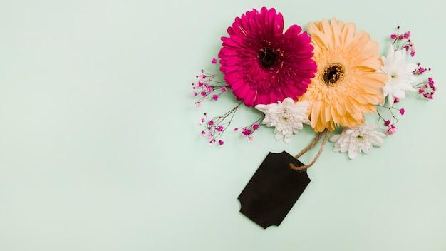 Decoração de flores com etiqueta preta sobre fundo verde pastel Foto gratuita