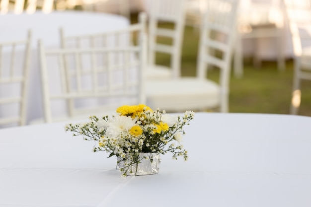 Decoração de flores na mesa branca ao ar livre na recepção do casamento Foto Premium
