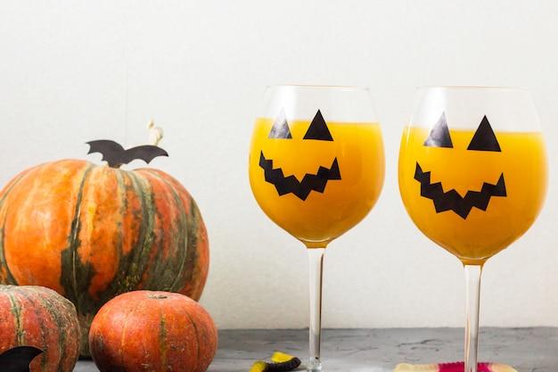 Decoração de halloween cocktail laranja abóbora de férias outono na mesa Foto Premium