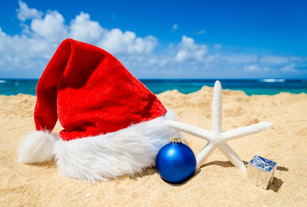 Decoração de natal com chapéu de papai noel e estrela do mar na praia Foto Premium