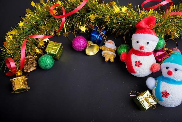 Decoração de natal com fundo preto escuro. vista superior, copie o espaço. bola, caixa de presente, papai noel, fita, ramo de pinheiro, sino, snowmans. Foto Premium