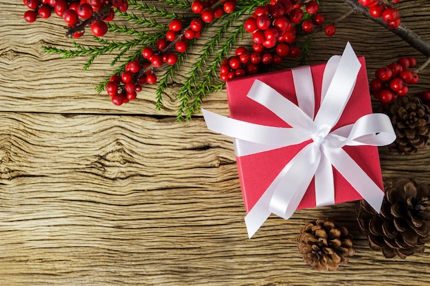 Decoração de natal da caixa de presente vermelha e winterberry vermelho na madeira velha Foto Premium