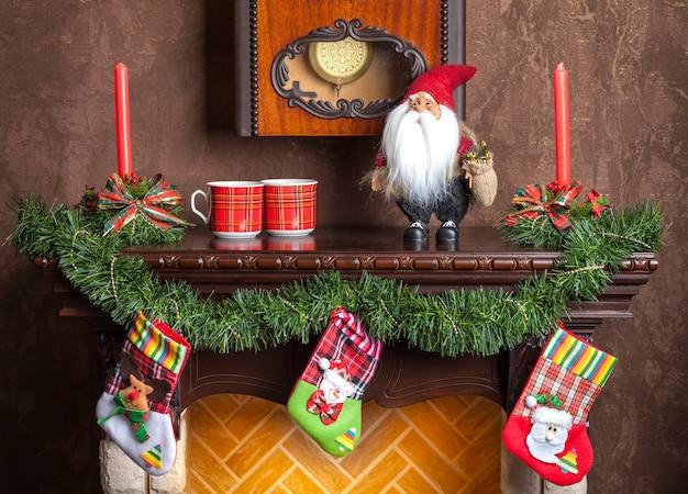 Decoração de natal de velas de lareira, garland e meias. Foto Premium