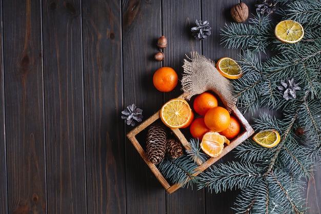 Decoração de natal e ano novo. laranjas, cones e galhos de árvores de natal Foto gratuita