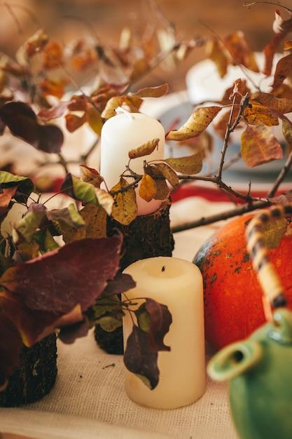 Decoração de outono com abóbora, velas e utensílios de mesa Foto Premium