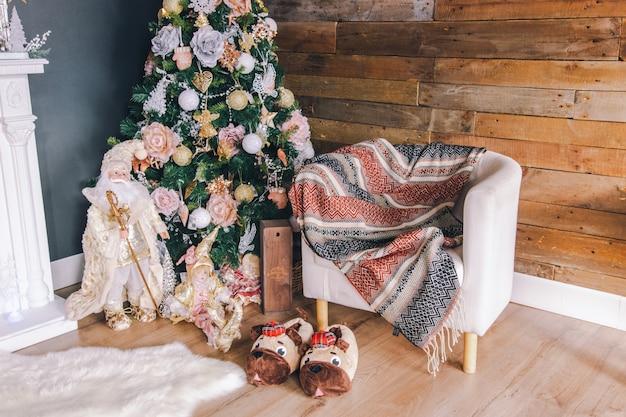 Decoração de quarto interior de ano novo ou natal: árvore de natal decorada, poltrona, chinelos e tapete. Foto Premium