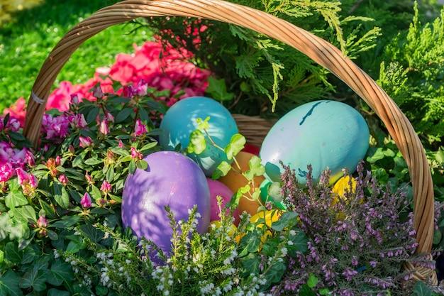 Decoração de rua de páscoa. cesta de vime cheia de ovos de páscoa pintados, bolo e flores. Foto Premium