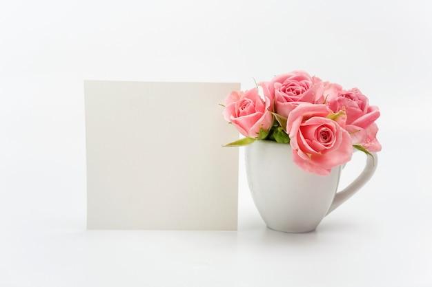 Decoração do lar, cartão vazio e copo com rosas Foto Premium