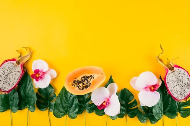 Decoração feita com papaia; frutas do dragão; orquídea e folhas artificiais em fundo amarelo Foto gratuita