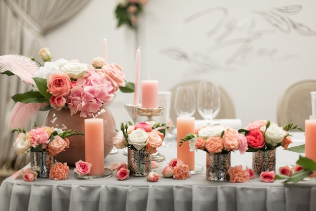 Decoração para a mesa de férias. castiçais de flores naturais nas cores rosa. Foto Premium