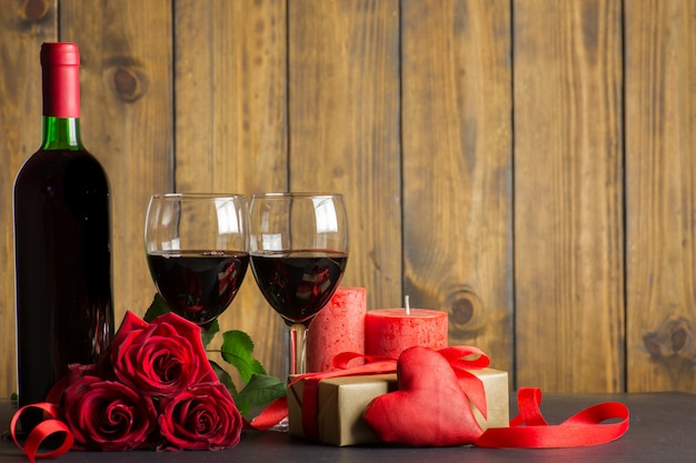 Decoração romântica de dia dos namorados com rosas, vinho e caixa de presente em uma mesa de madeira marrom Foto Premium