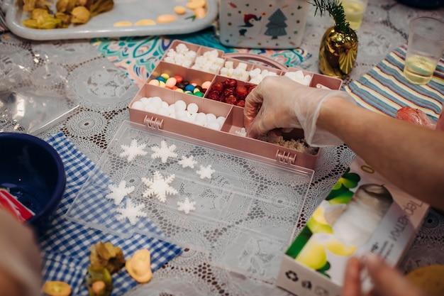 Decorações comestíveis de natal, para decoração de bolos. fechar as mãos do chef pasteleiro. atmosfera de feriado de natal. ambiente de trabalho. confusão criativa Foto Premium