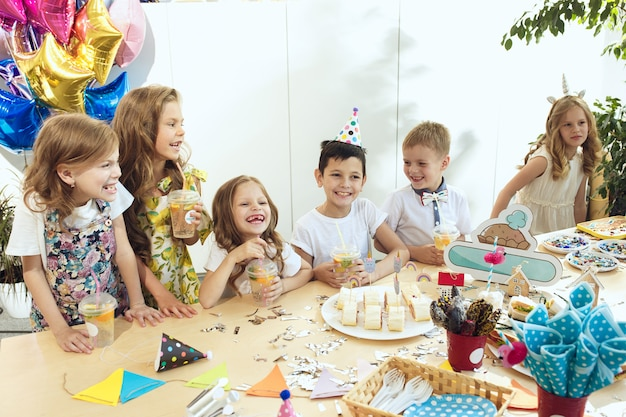 Decorações de aniversário de menina. mesa com bolos, bebidas e acessórios para festas. Foto gratuita