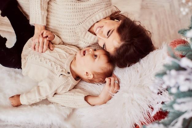 Decorações de férias de inverno. cores quentes. retrato de família. mãe e filha adorável Foto gratuita