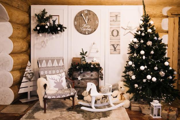Decorações de natal: cadeira, árvore de natal, cômoda, relógio, presentes no fundo de uma parede de madeira. zona de foto de natal. zona de foto de natal com uma árvore de natal. Foto Premium