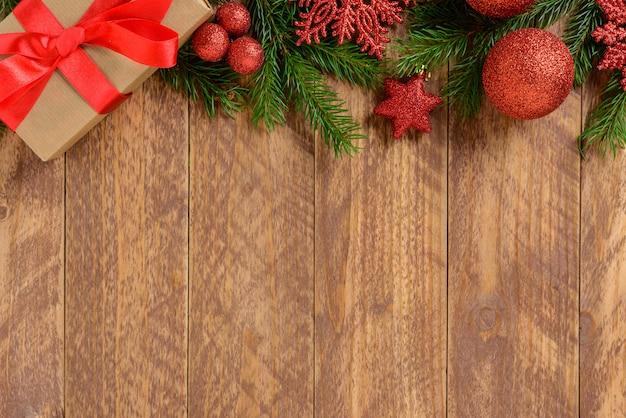 Decorações de natal, caixa de presente e bolas vermelhas em uma mesa de madeira marrom. vista superior, copie o espaço. Foto Premium