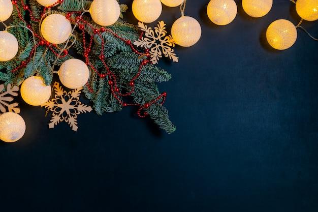 Decorações de natal com árvore do abeto, brilhante guirlanda e flocos de neve em fundo preto com copyspace Foto Premium