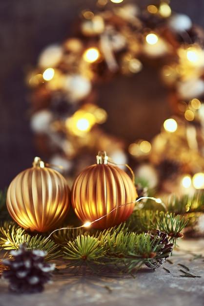 Decorações de natal com bolas douradas, galho de árvore do abeto e luzes de guirlanda em um escuro Foto Premium