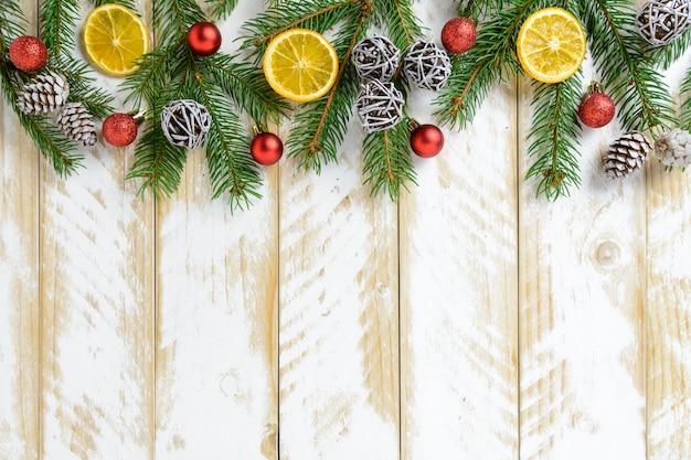Decorações de natal, pinhas e frutas laranja em uma mesa de madeira branca. vista superior, copie o espaço. Foto Premium
